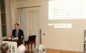 Professor Roger Stalley during his lecture with text from the Book of Kells in the background