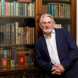 Professor Thomas Bartlett standing in front of Princess Grace's Personal Collection of Irish books